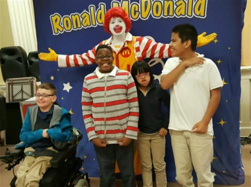 Four students with Ronald McDonald in auditorium