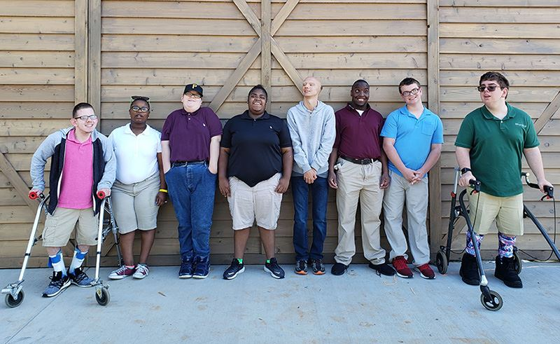 A group of AIDB students stand in front of the barn door of the new JTA Agriscience Center